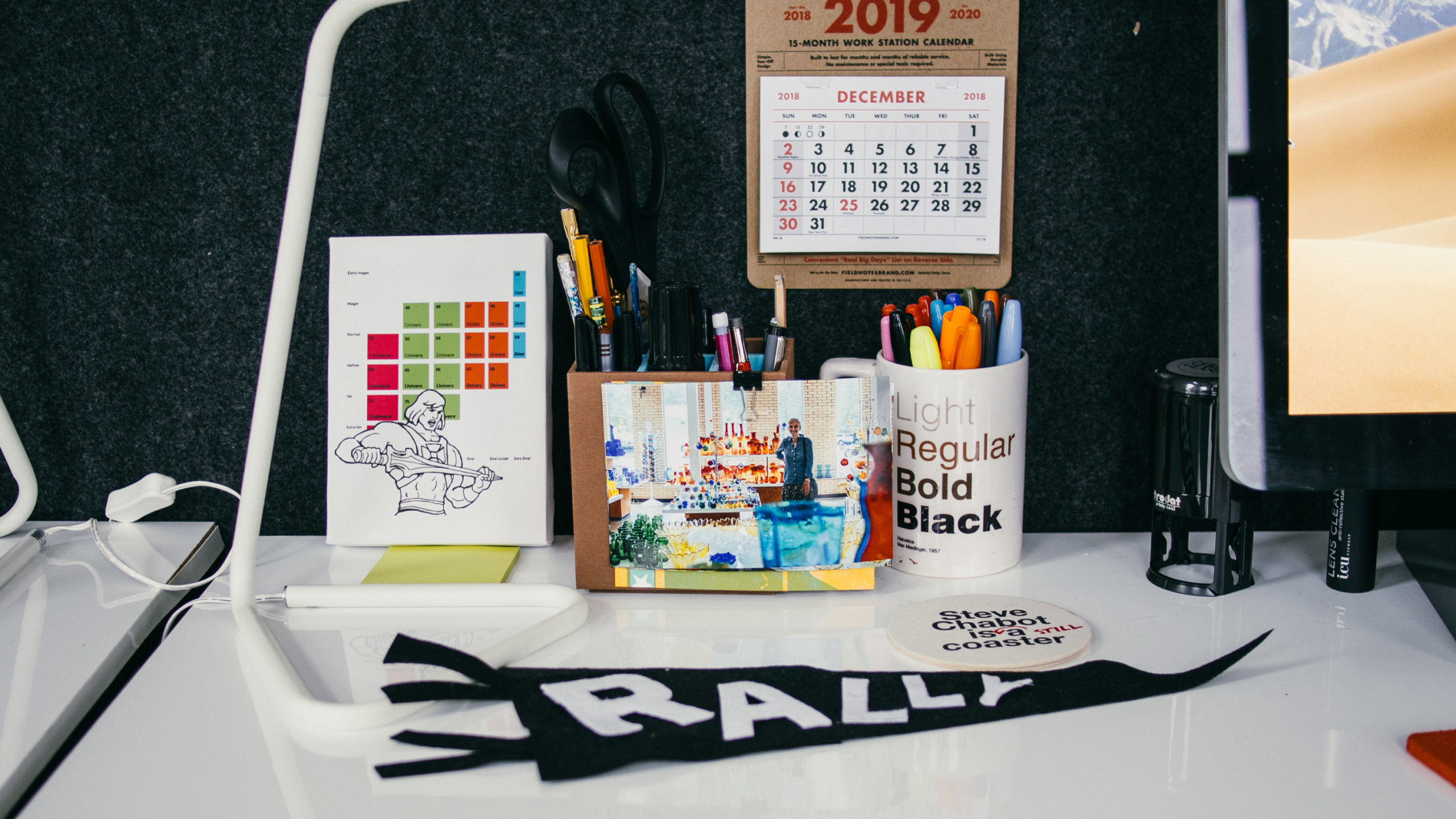 A desk with accessories like a calendar in a cup filled with pins