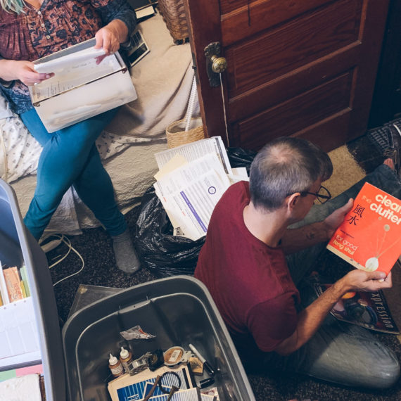 A woman and man sorting through boxes and photographs