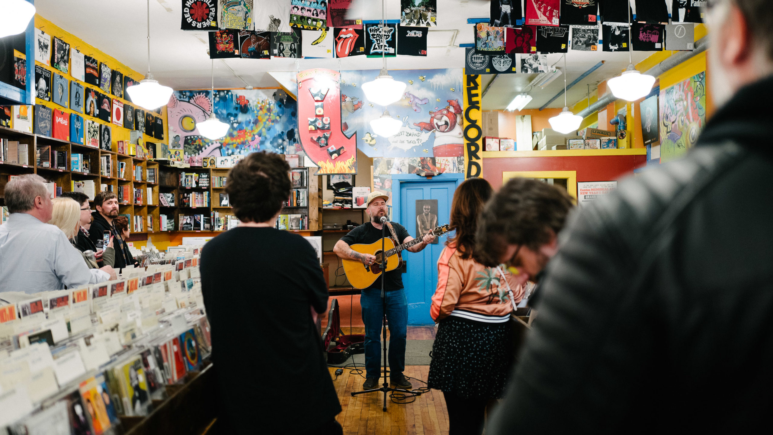 A man with an acoustic guitar gives a performance in a record store to a crowd