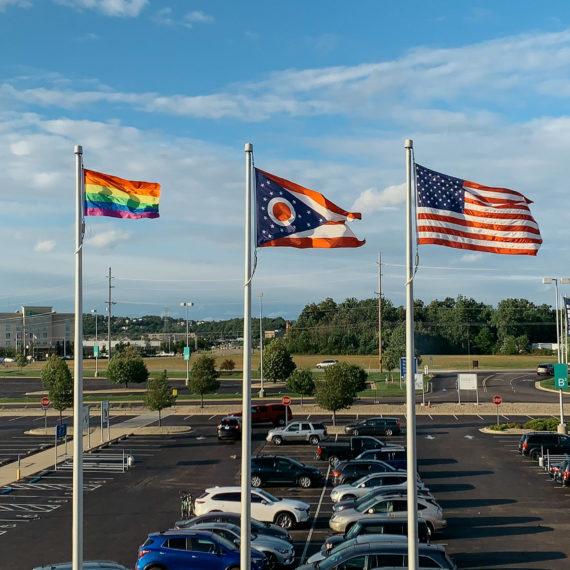 A rainbow flag, Ohio flag and US flag
