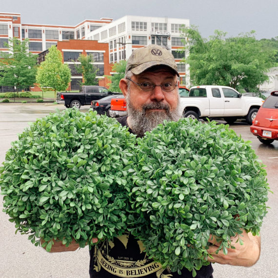 Man holding fake shrubs