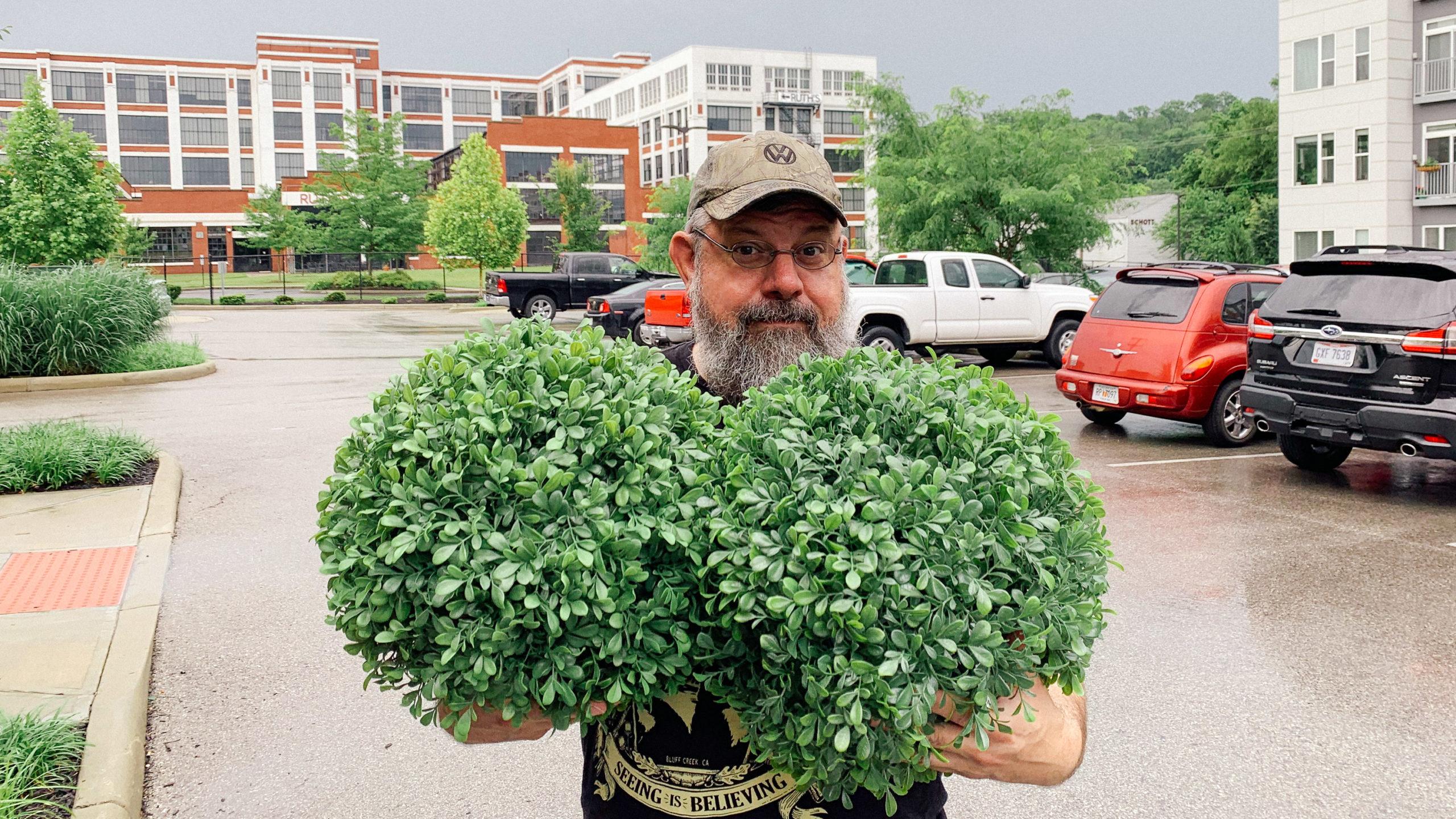 Man holding fake shrubs
