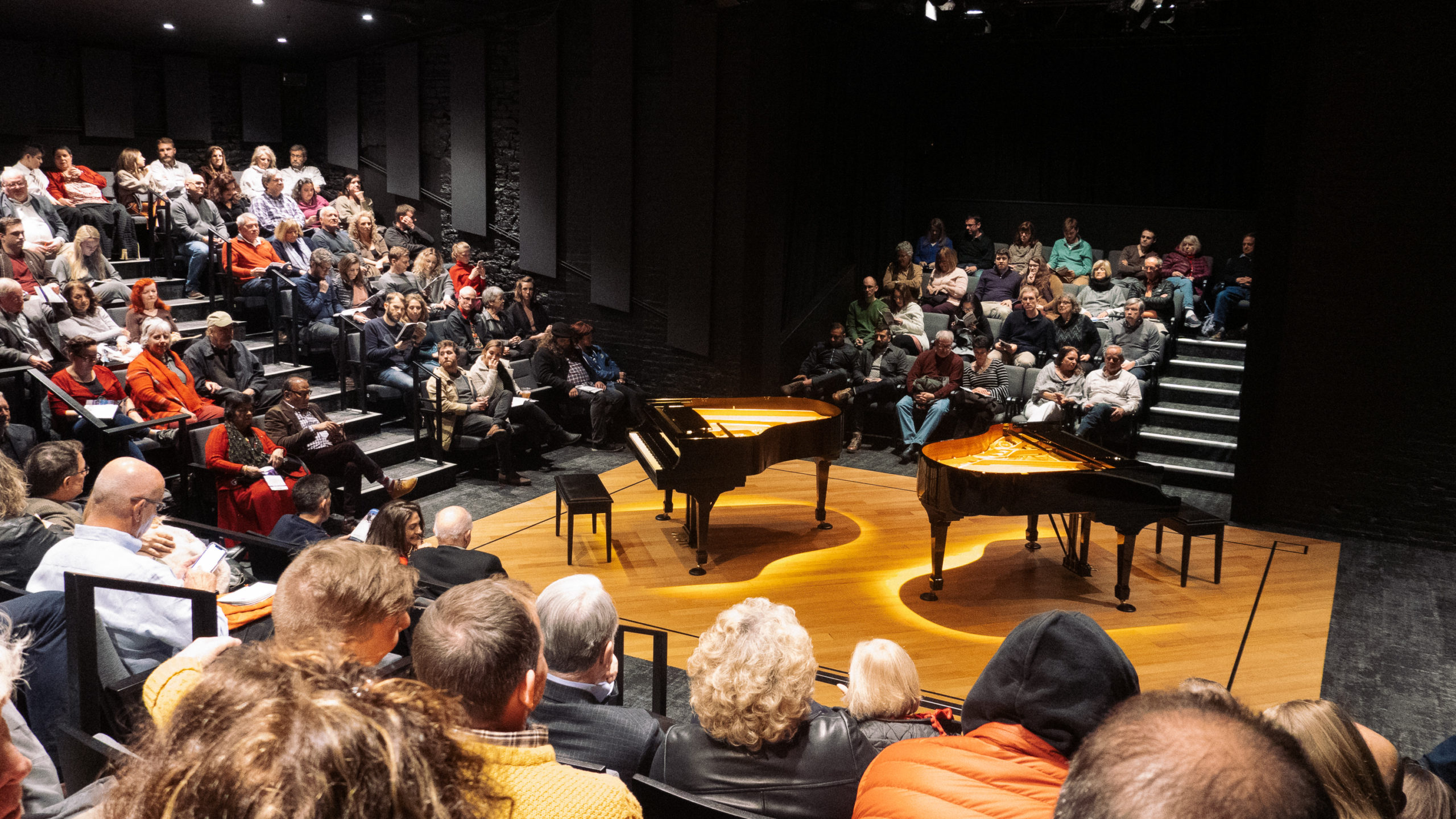 Two pianos set up on a stage in a theater in the round