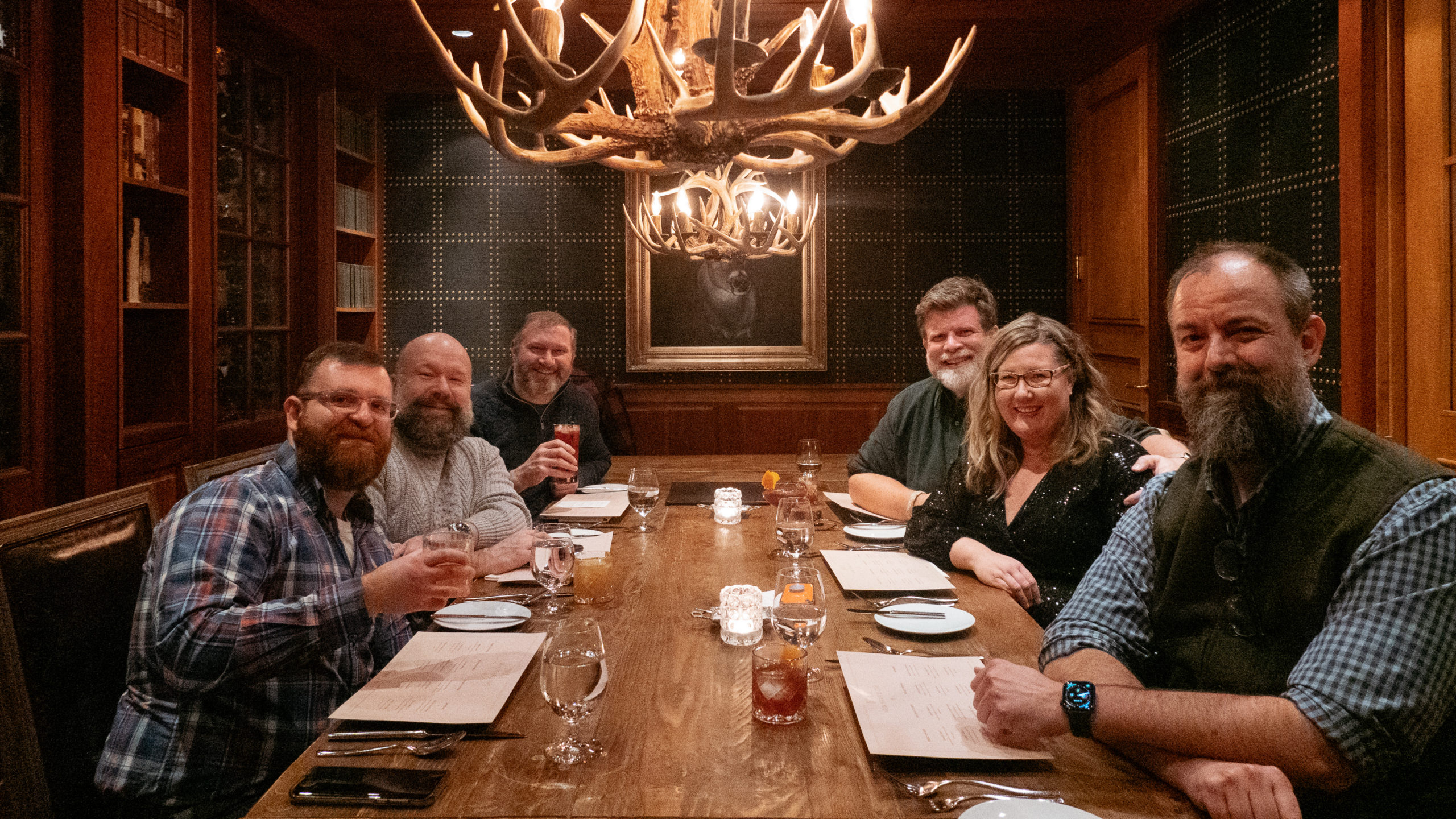 A group of bearded men and a woman at a restaurant table
