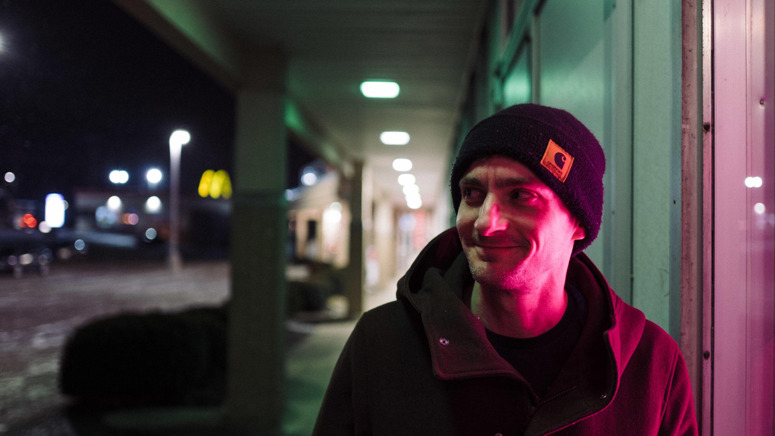 man lit by neon light
