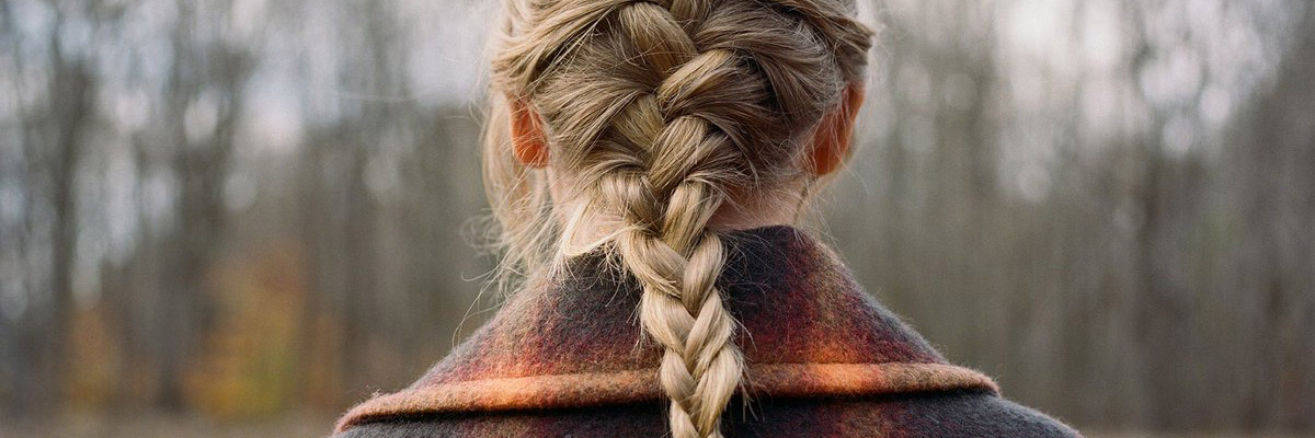 The back braid of a woman in a plaid winter coat