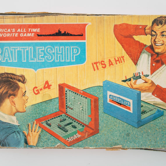 An old beat up board game box for Battleship from Milton Bradley