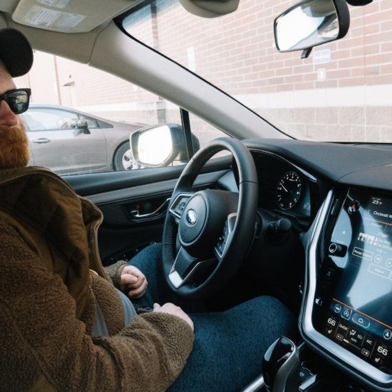 A bearded man behind the wheel of a Subaru Outback