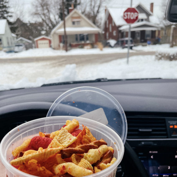 A person holding a plastic cup filled with snack mix in their car