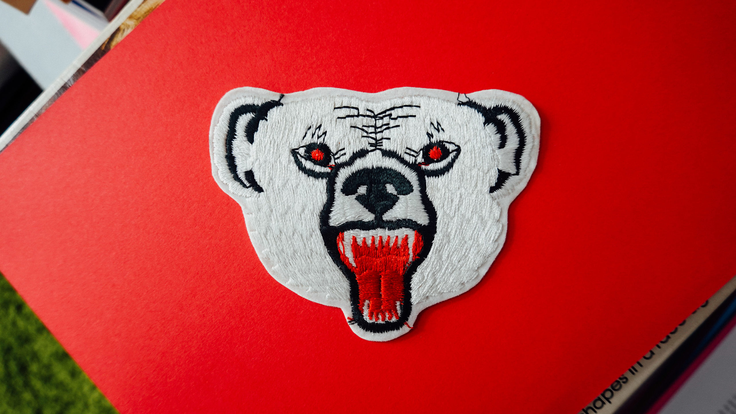 A patch of a polar bear on a red background.
