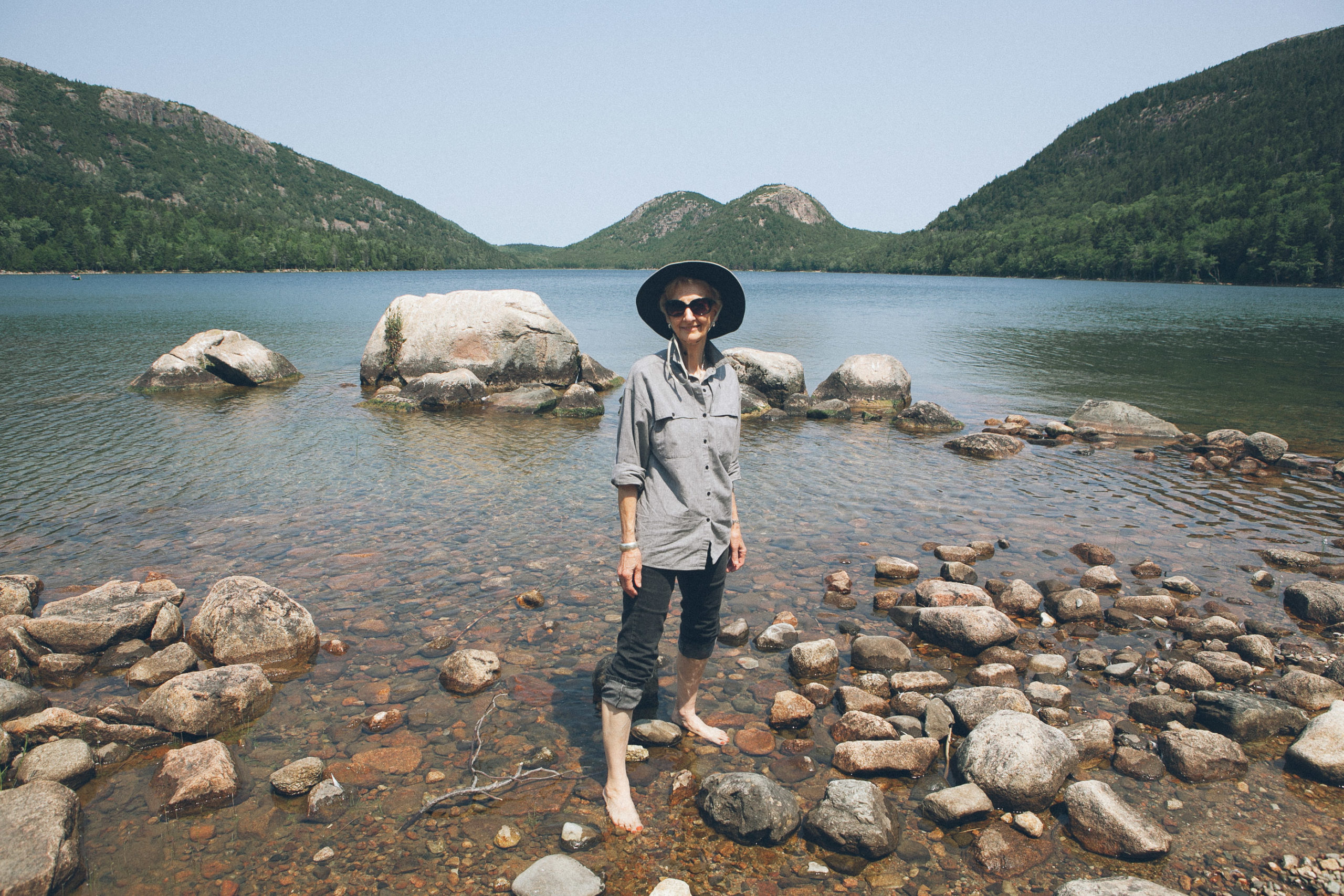 A woman with her pants rolled up to walk in the water of Jordan Pond