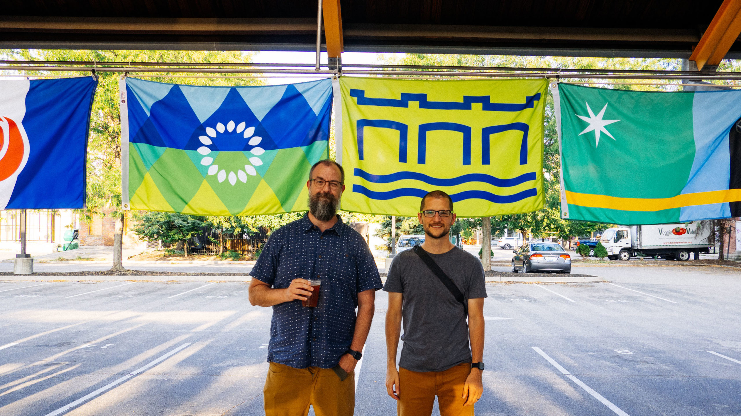 Two white men standing in front of colorful flags