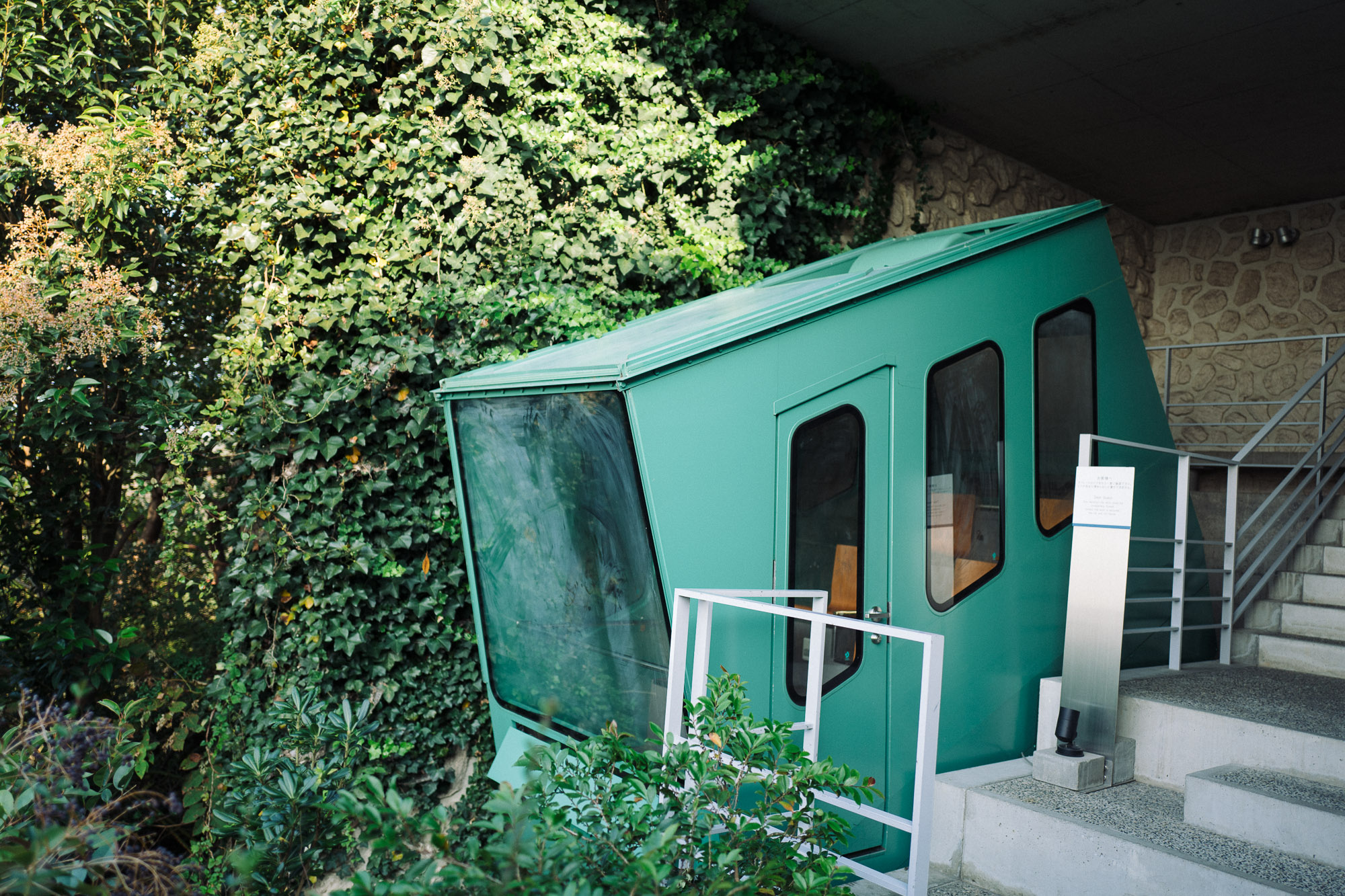 A teal funicular in lots of greenery