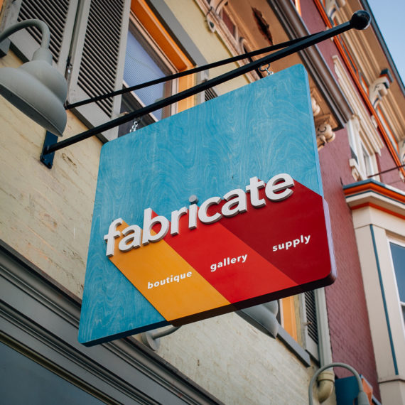 A colorful sign that says Fabricate