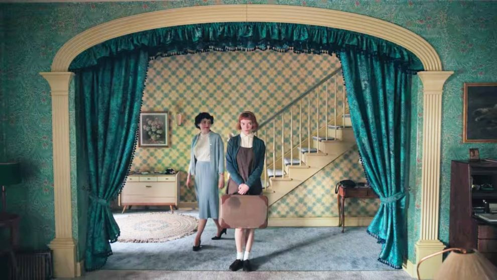 A very stylized entry way of a 1960's house in teal. Two women stand near the center of the frame.