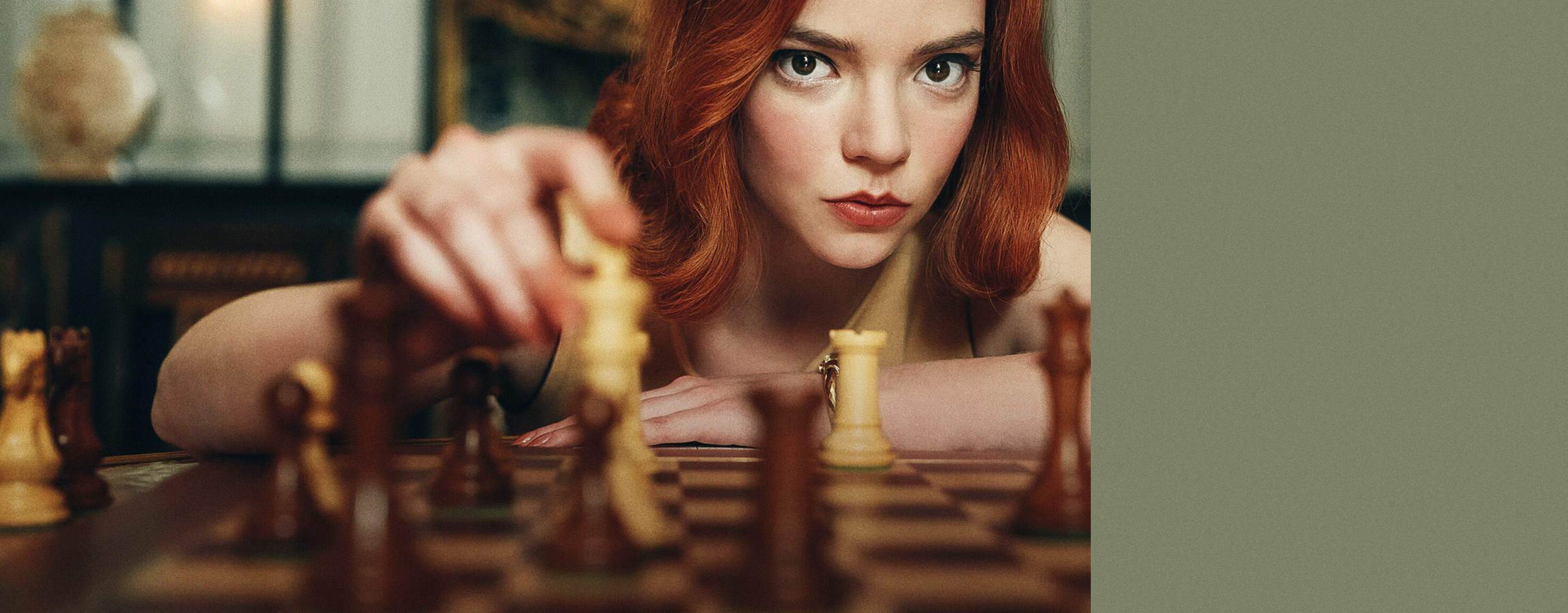 A woman with red hair holds a bishop chess piece
