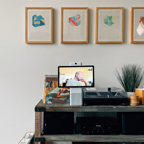 A monitor with a man looking bored next to a record player and 4 framed graphic prints