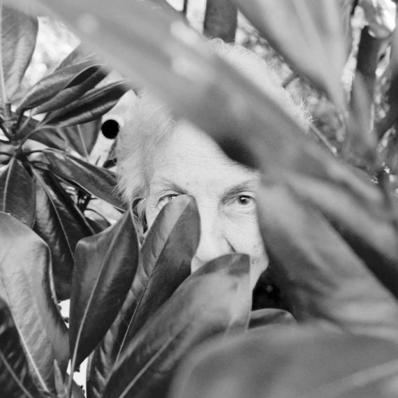 Woman hiding behind leaves of a magnolia tree