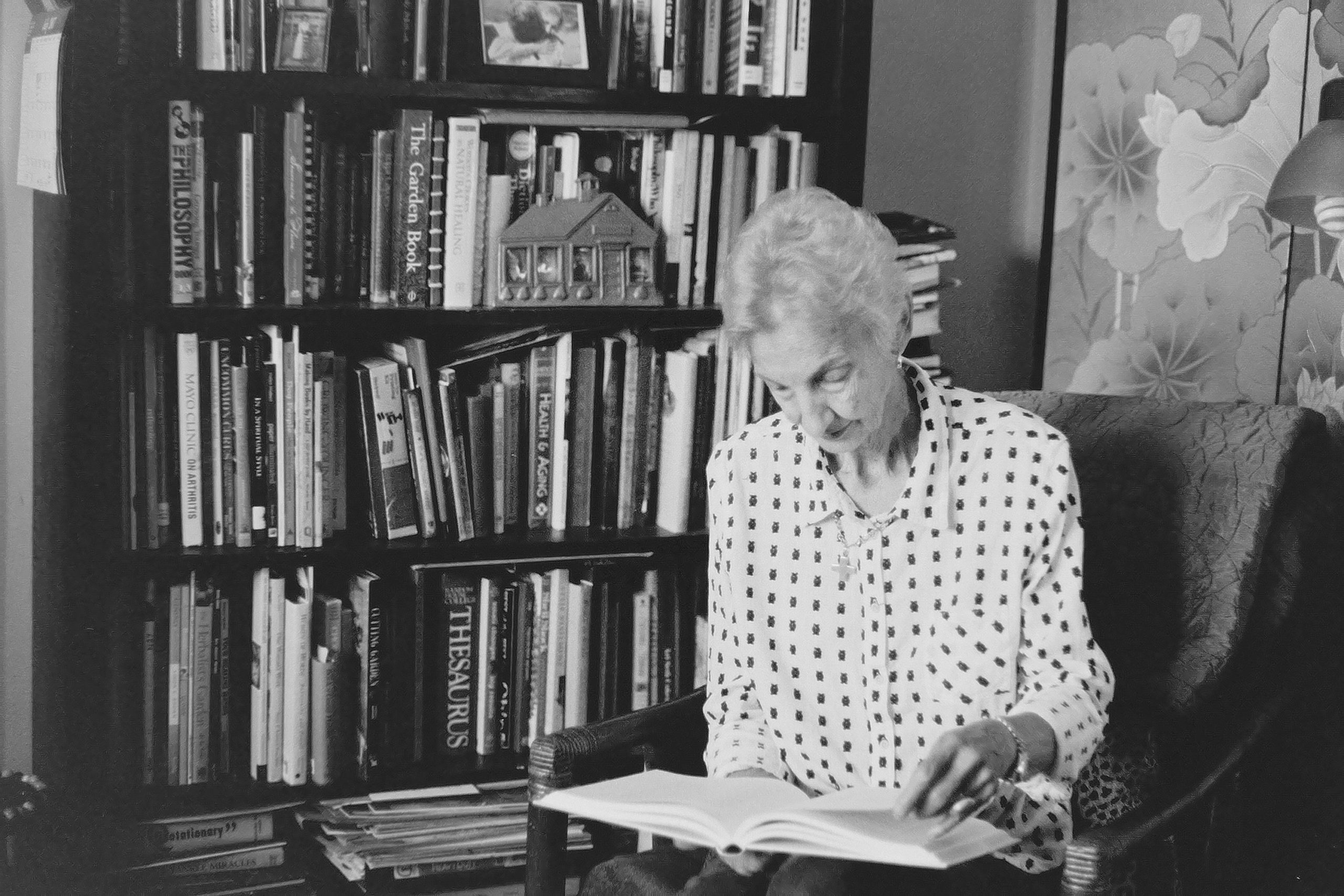 A black and white photo of a woman reading a book