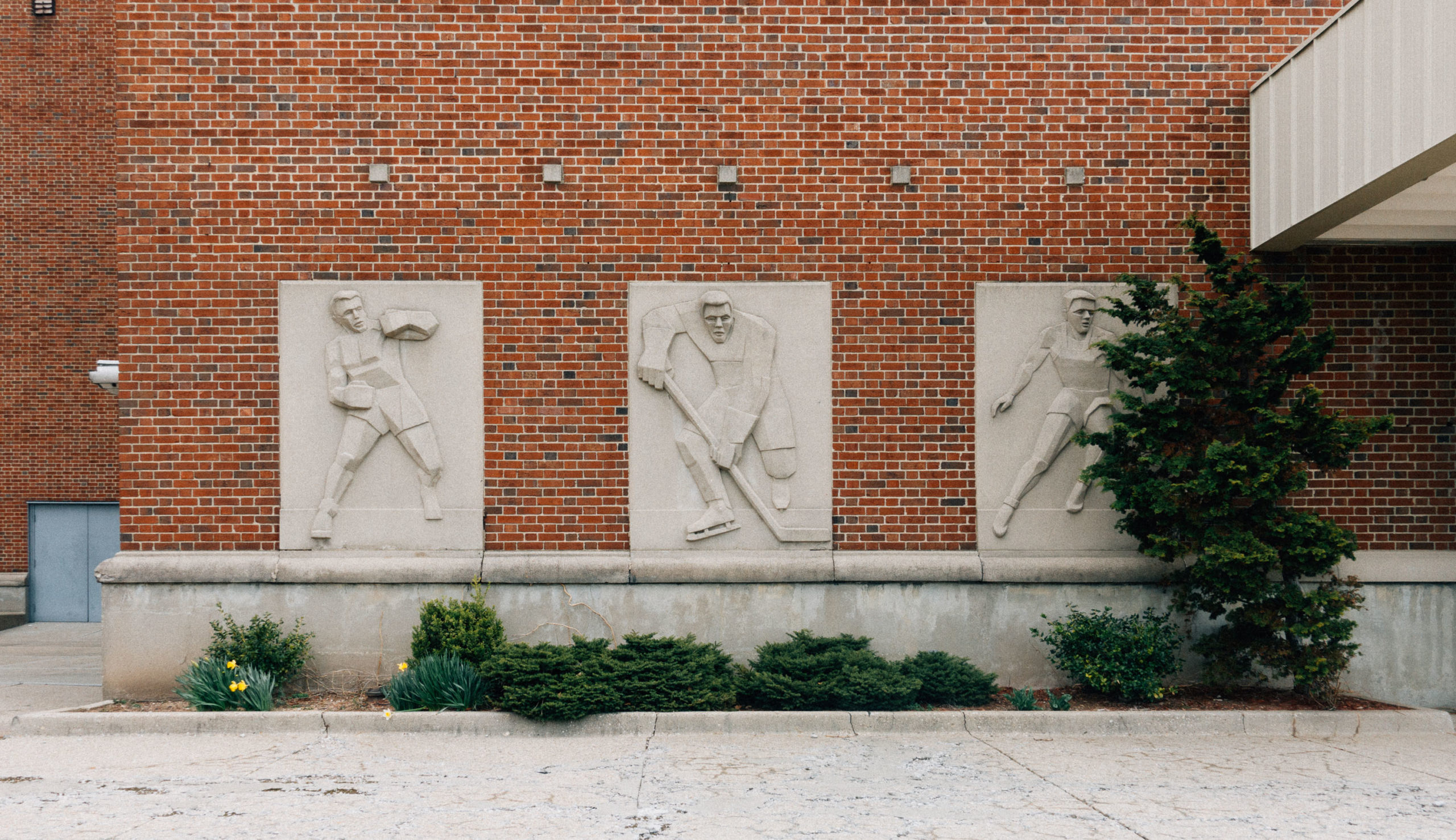 Details of sports relief figures on a brick building