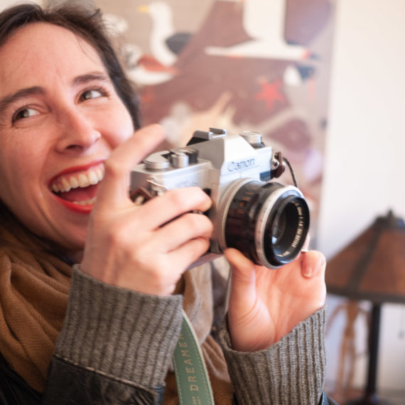 Woman smiling with Canon film camera