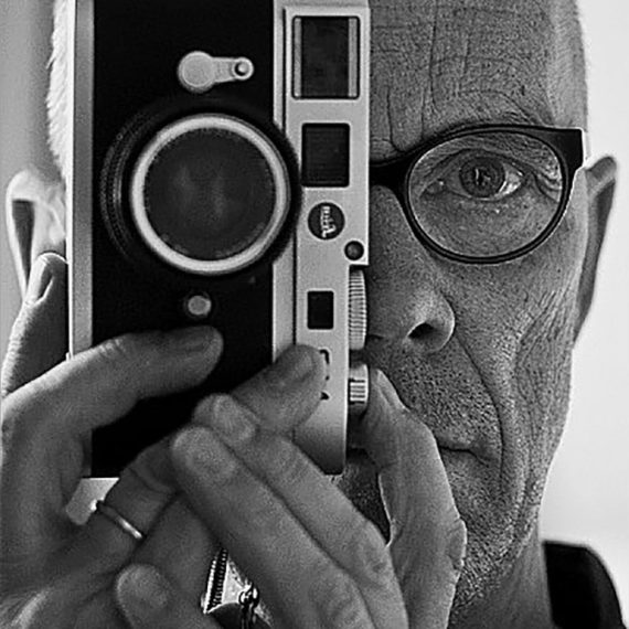 A man holding a film camera up to his eye