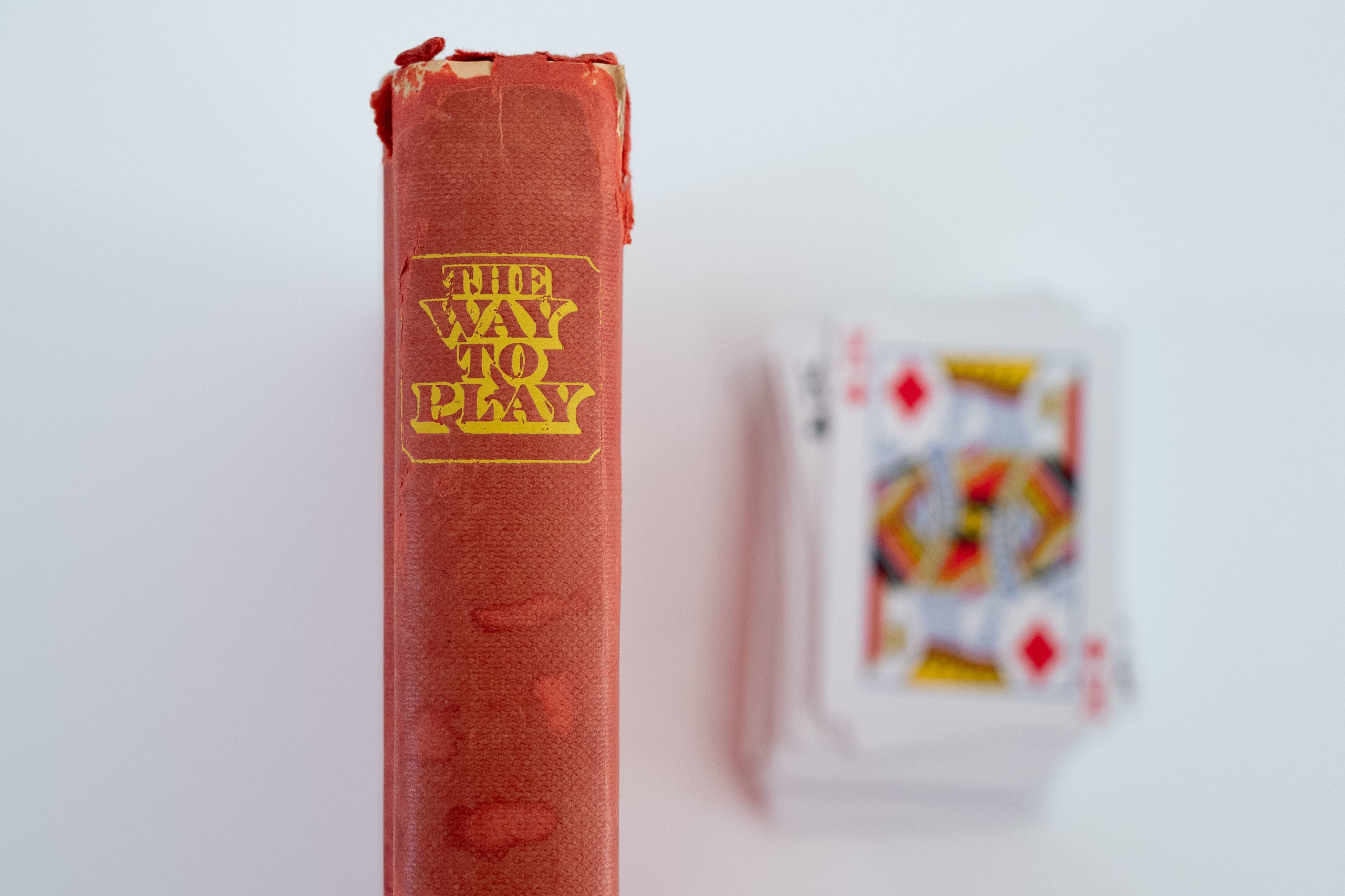 "The spine of a book ""The Way to Play"" and a blurry deck of playing cards"