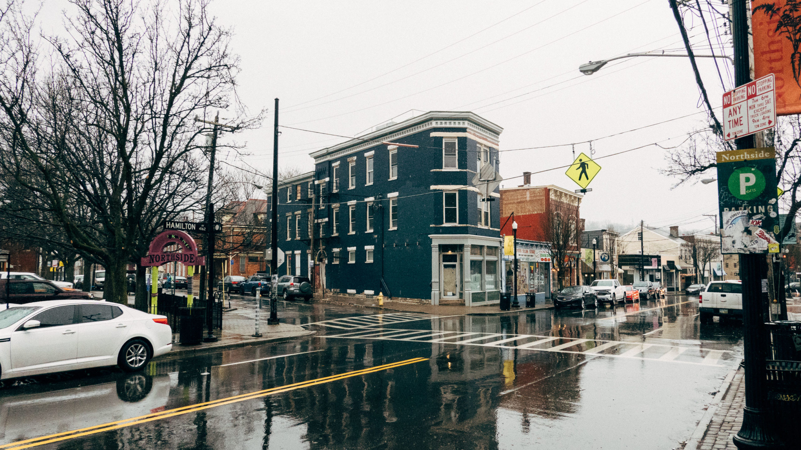 A corner building in a neighborhood reflected in the rain soaked street