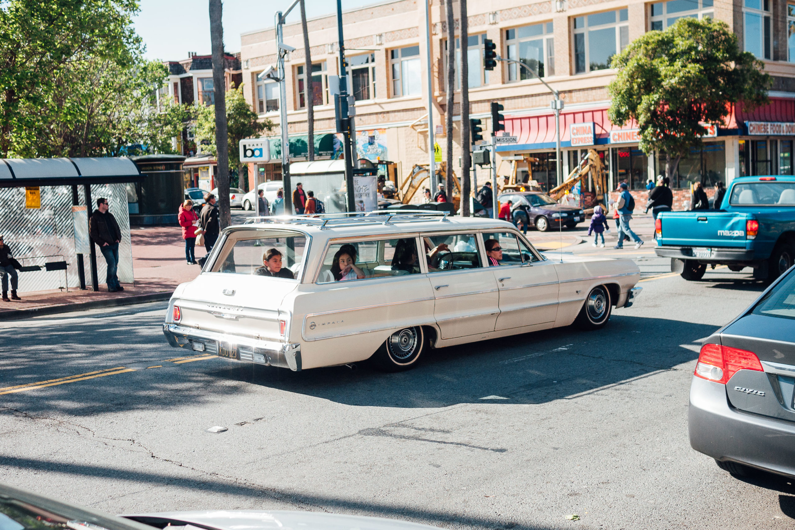A family in a classic Impala station wagon