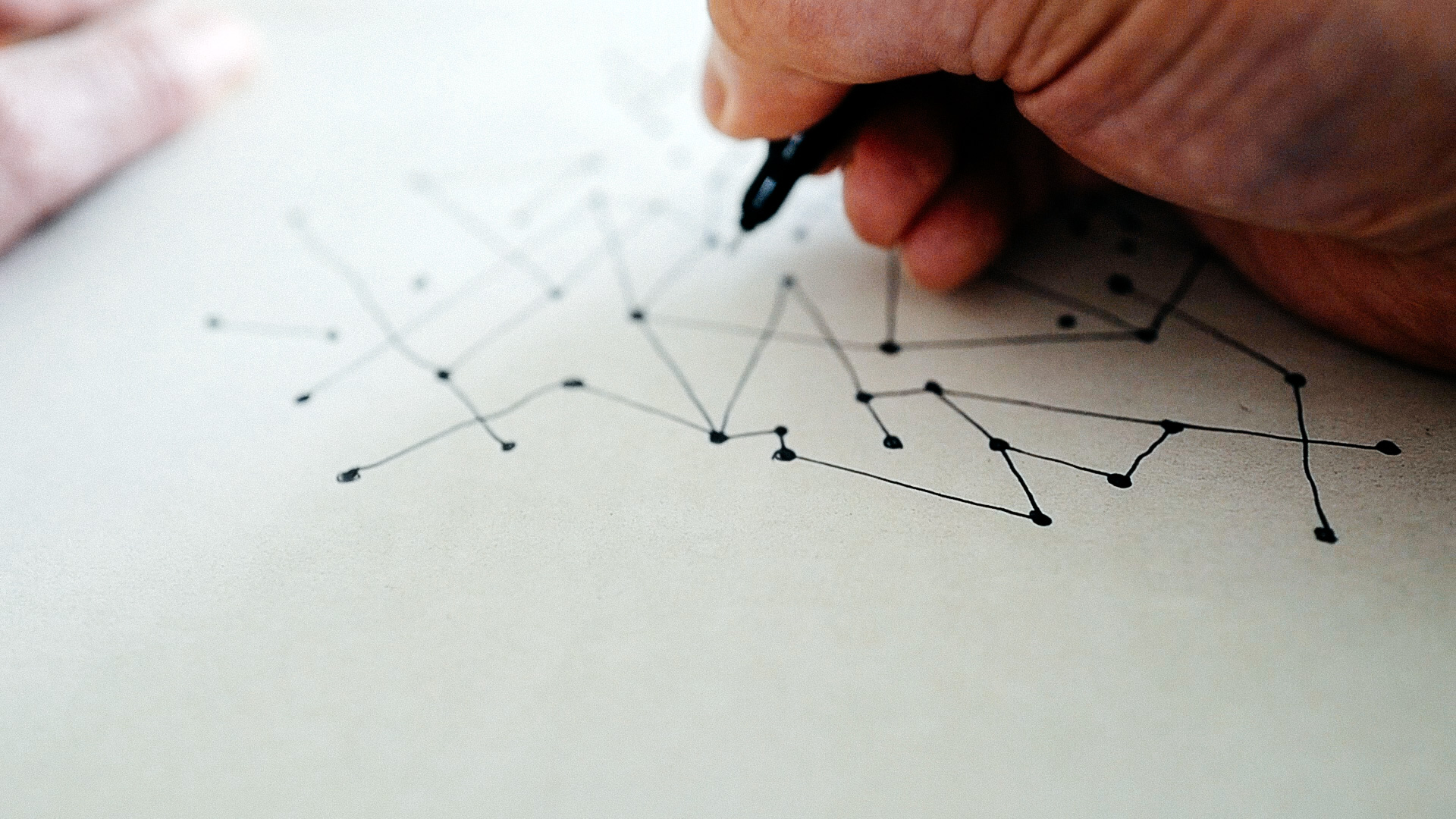 A hand with a pen, connecting lines and drawing circles