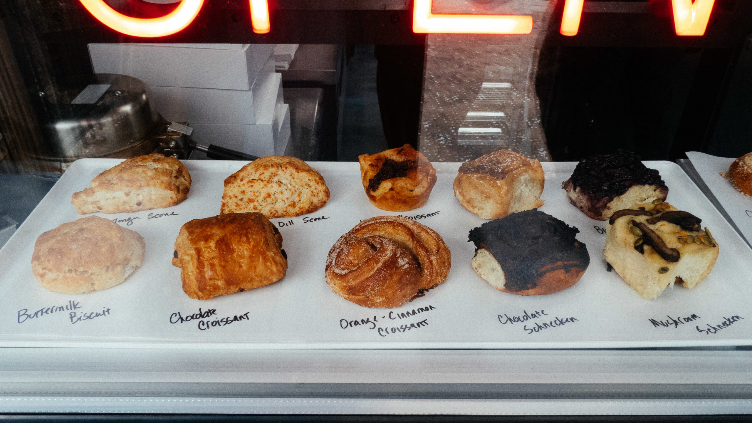 Baked goods on display behind a pane of glass