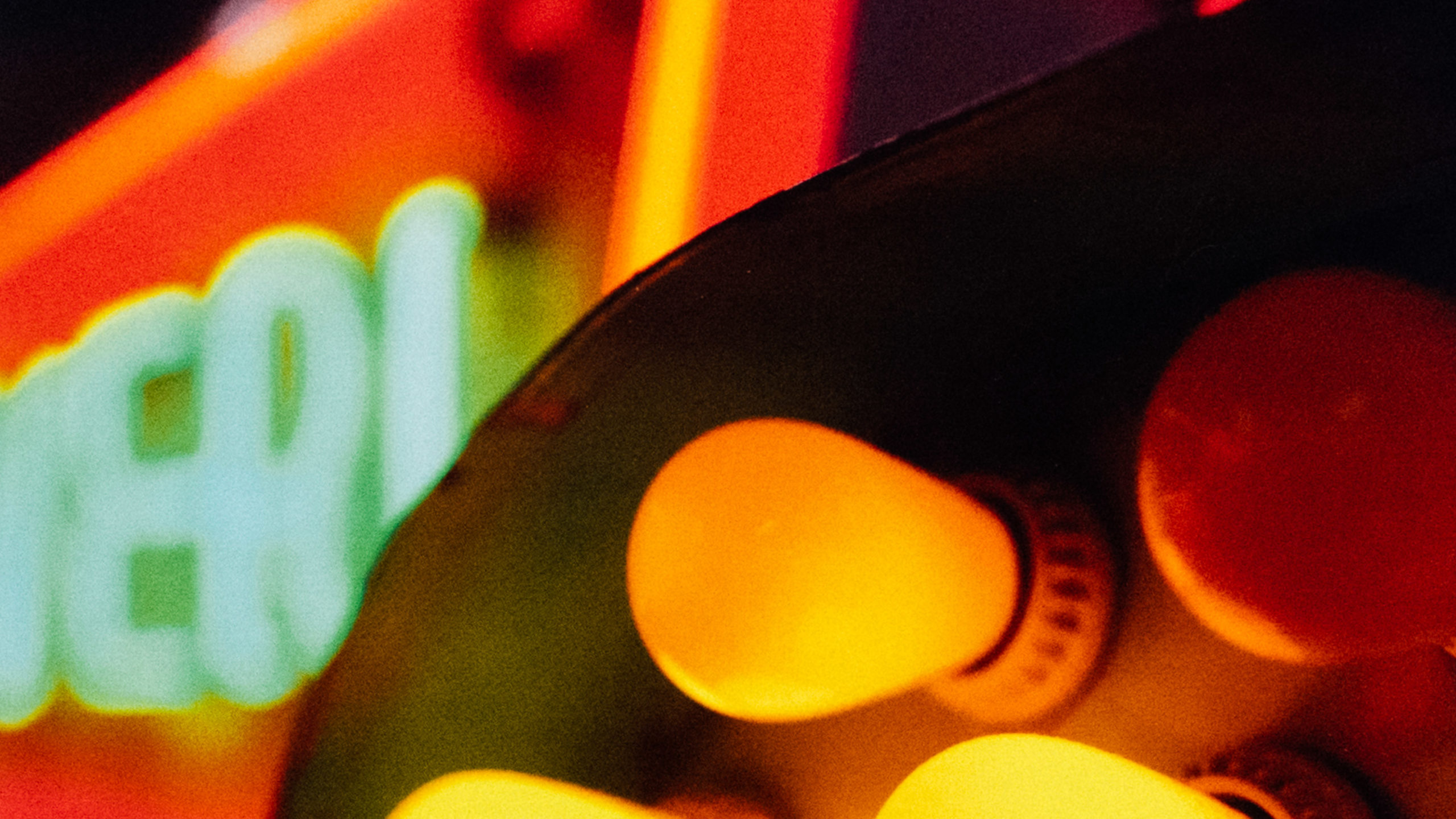 Closeup of a light bulb with neon lights blurred in the background