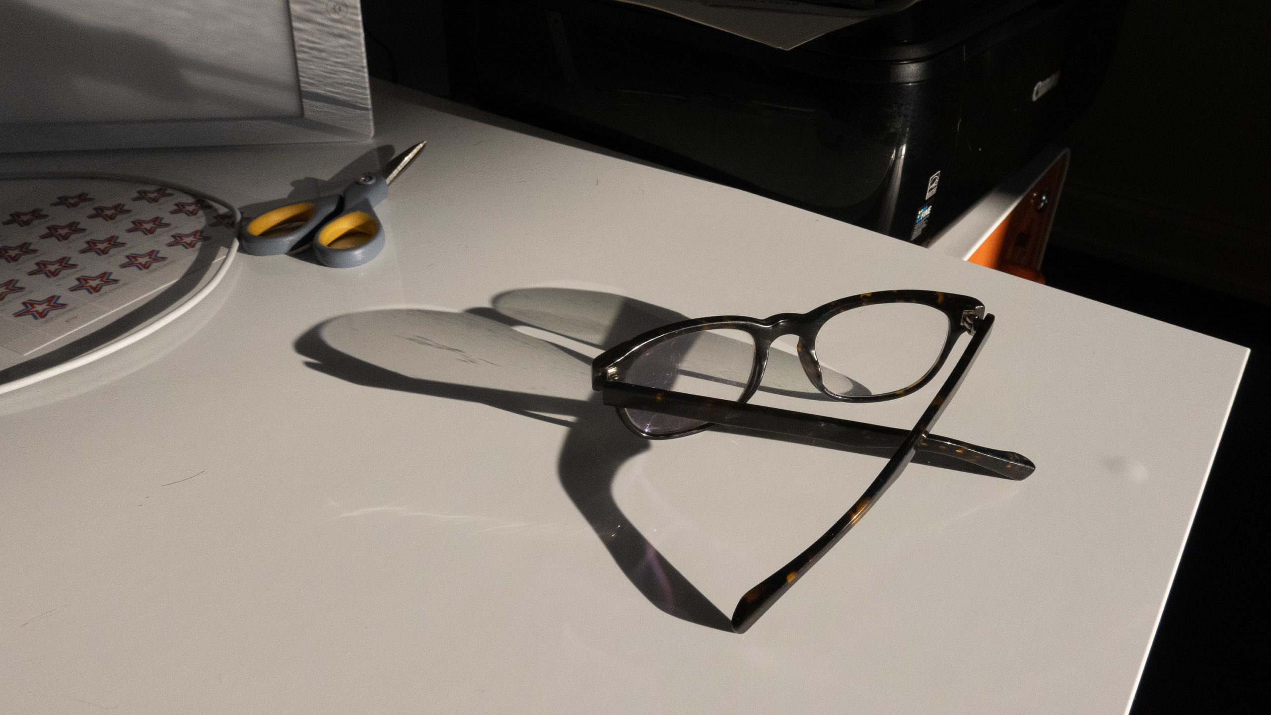 A pair of glasses on a white desk with a long shadow from evening light