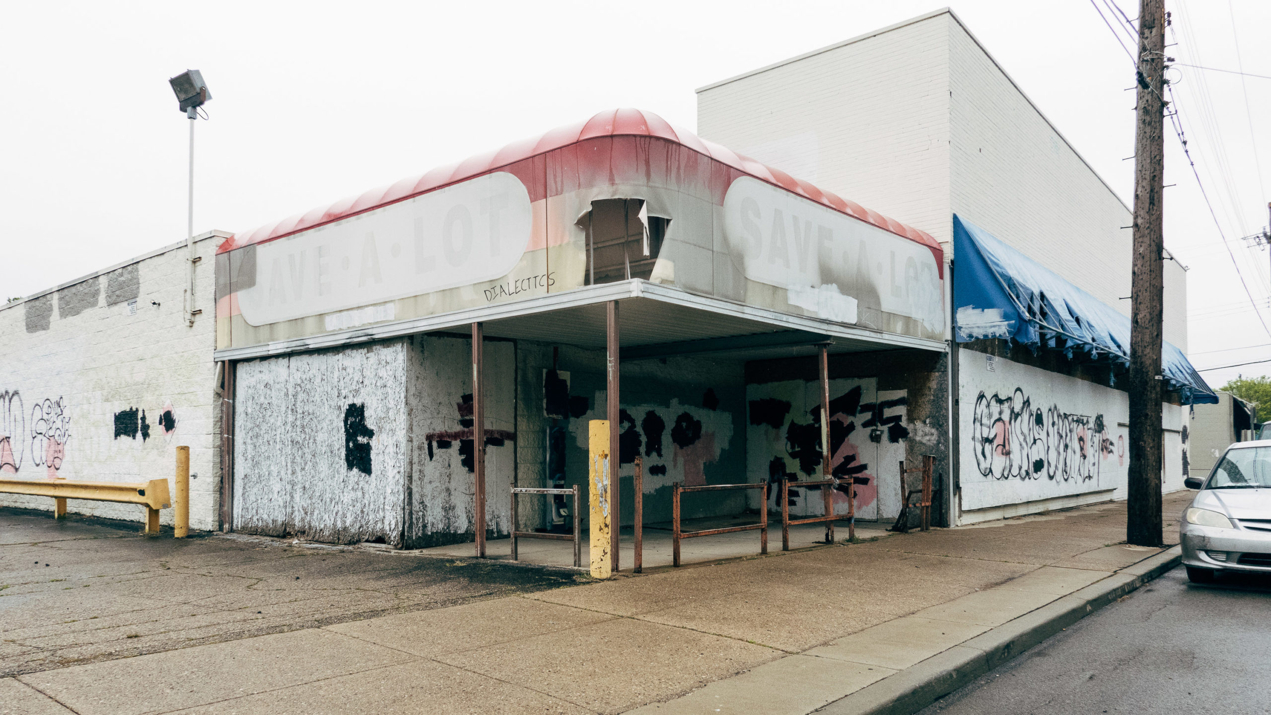 A closed grocery store covered in covered up graffiti