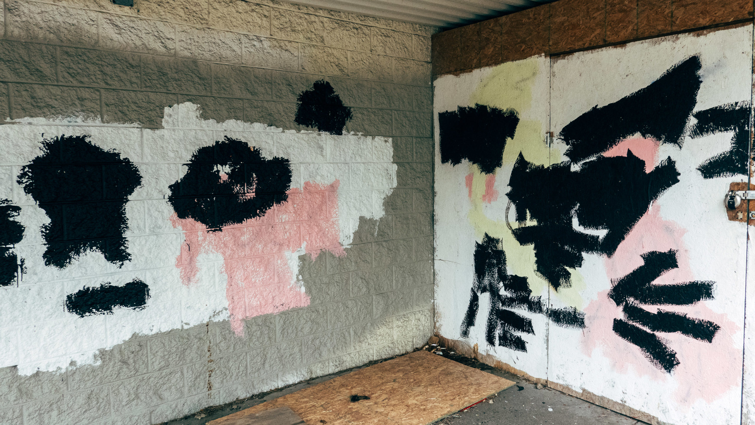 Graffiti covered up with white, pink and black paint