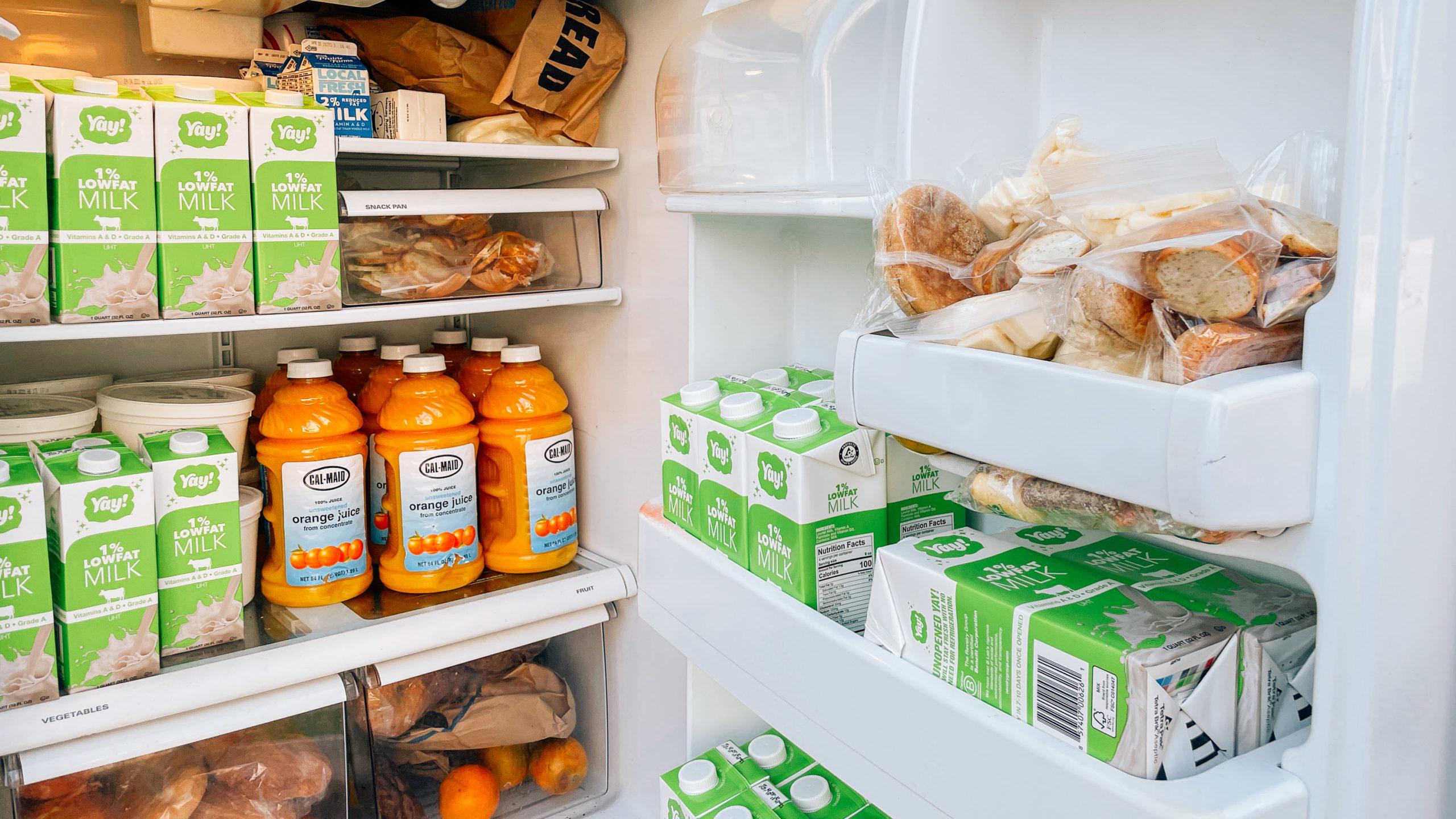 A public fridge door open, filled with free food
