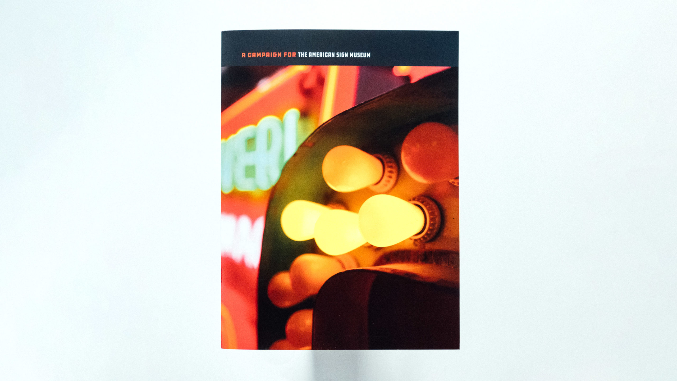 American Sign Museum prospectus cover featuring a photograph of a sign with light bulbs