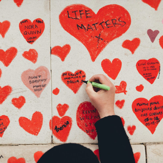 Woman writing inside a heart painted on a wall