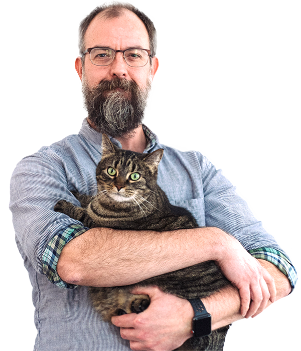 A balding bearded man holding a slightly surprised cat