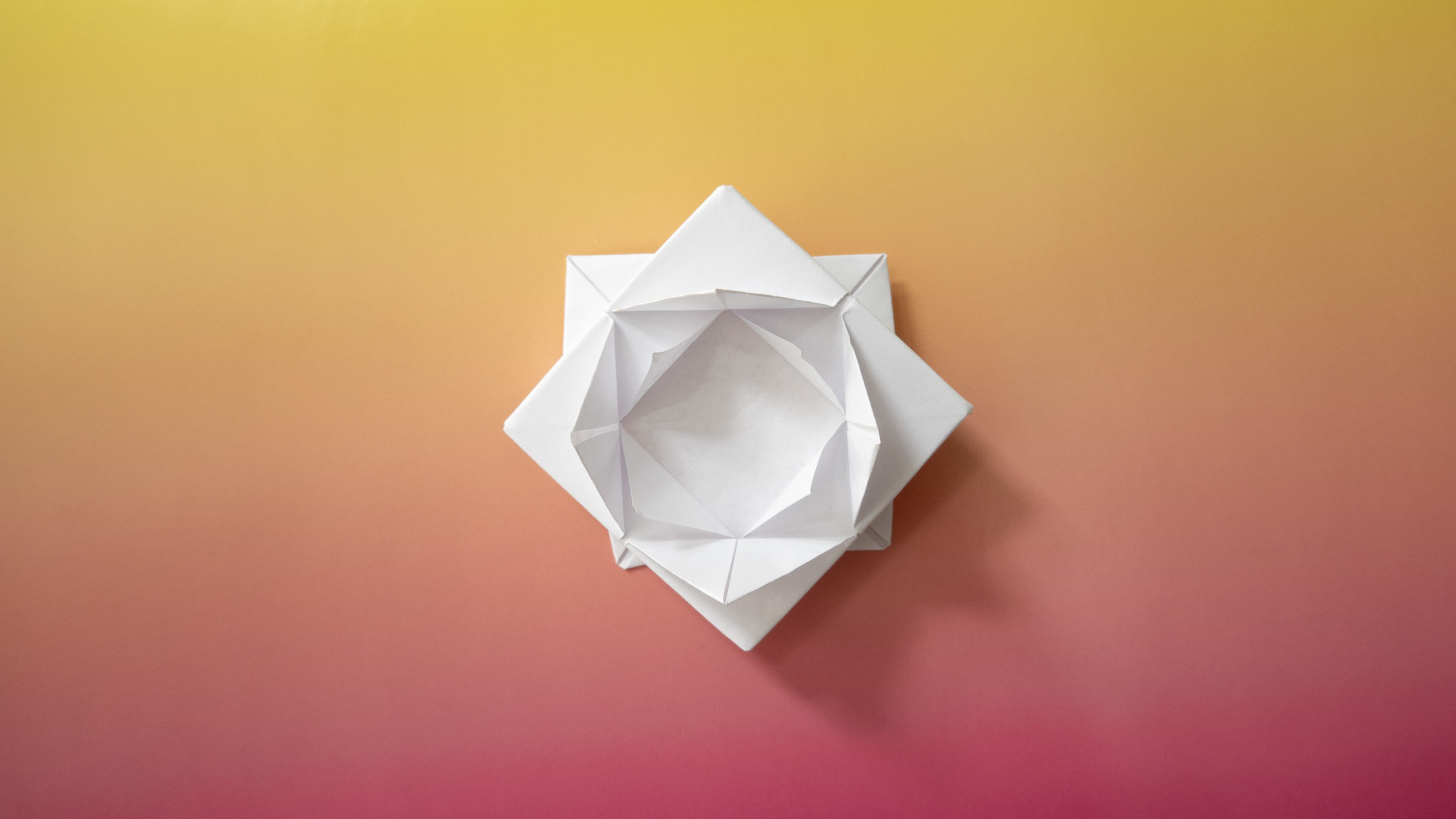 A white origami lotus flower on a gradated sheet of paper