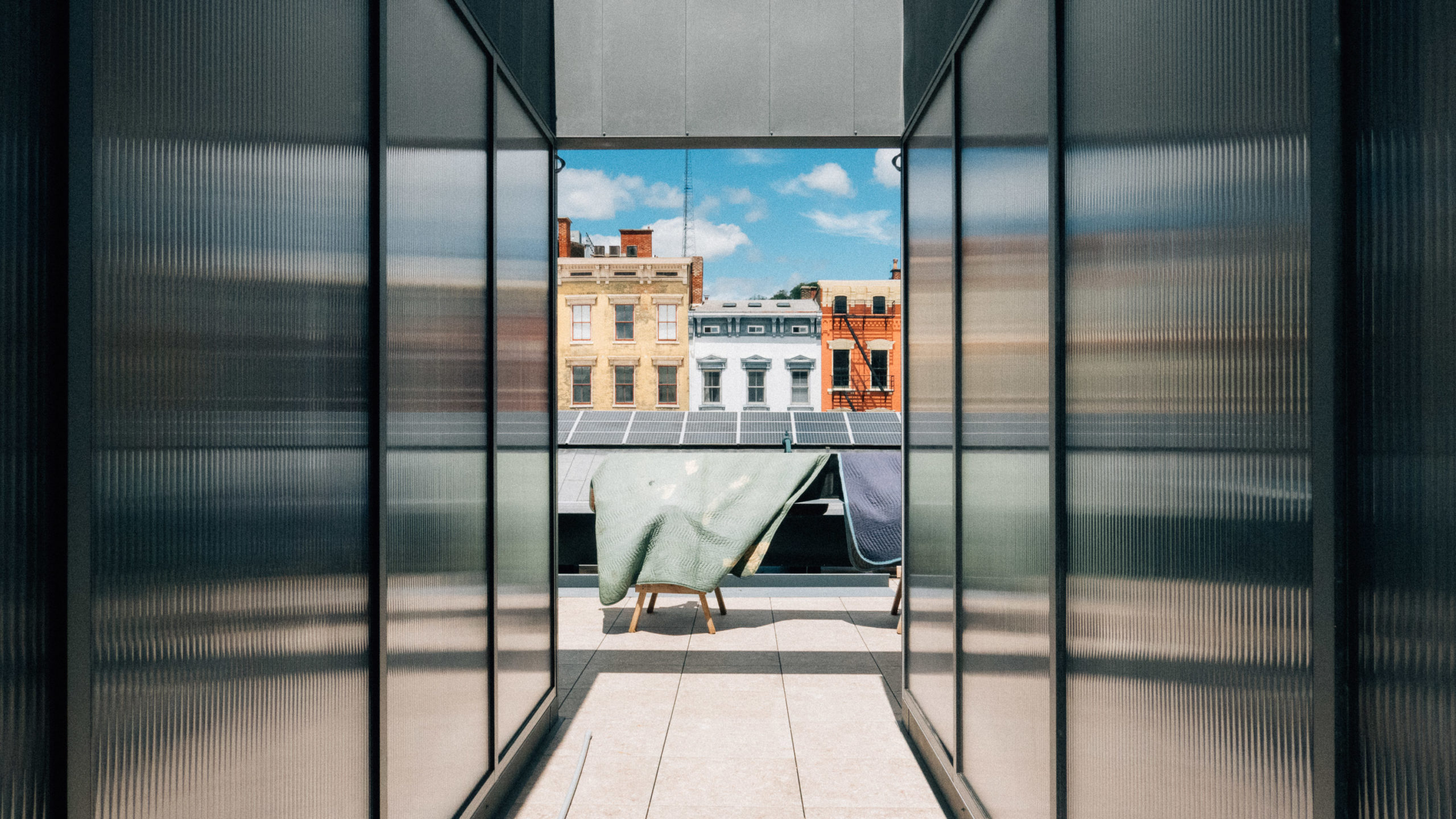 An exterior hallway of reflective surface leading to a city view