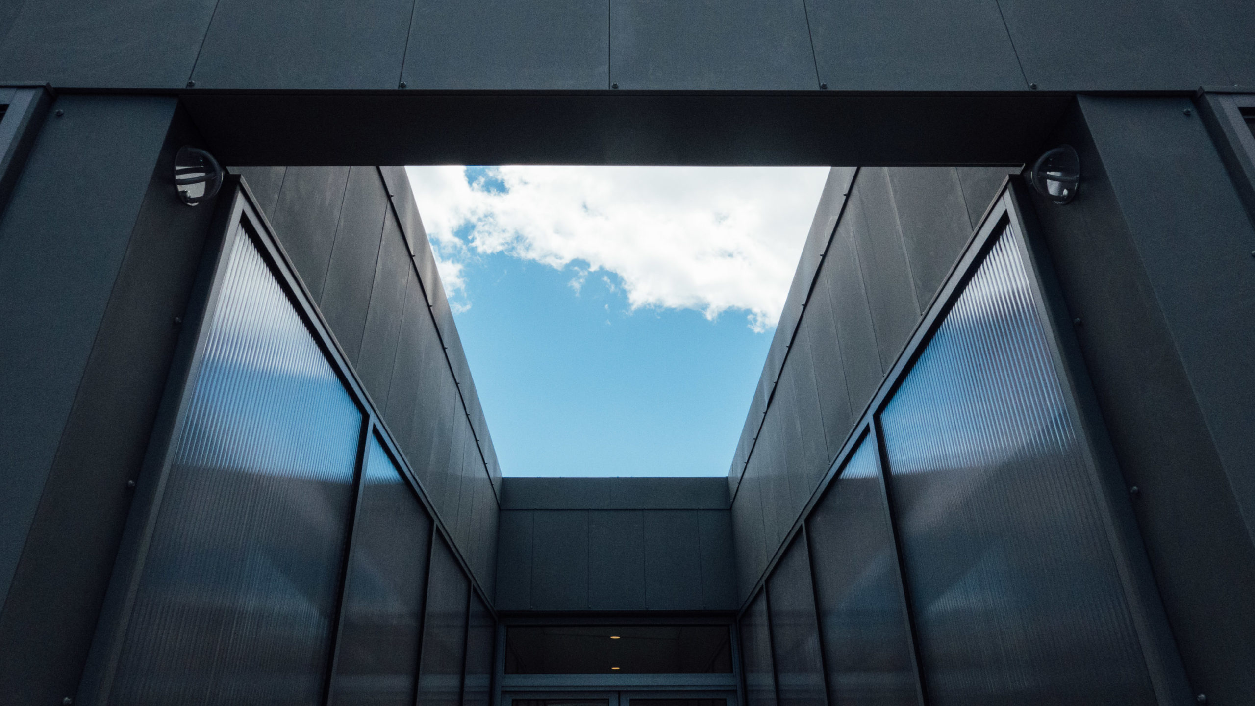 A geometric open roof revealing a blue sky with clouds