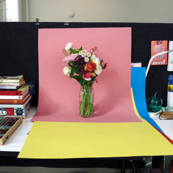 A bouquet of flowers on a pink sheet of poster board