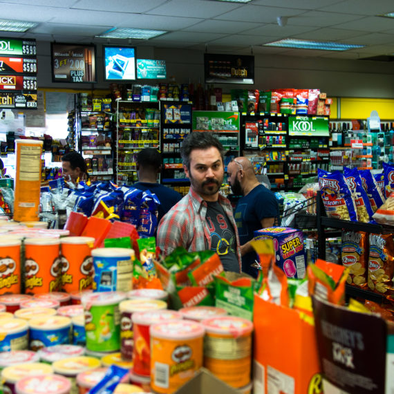 Man standing in aisle of a crowded mini mart