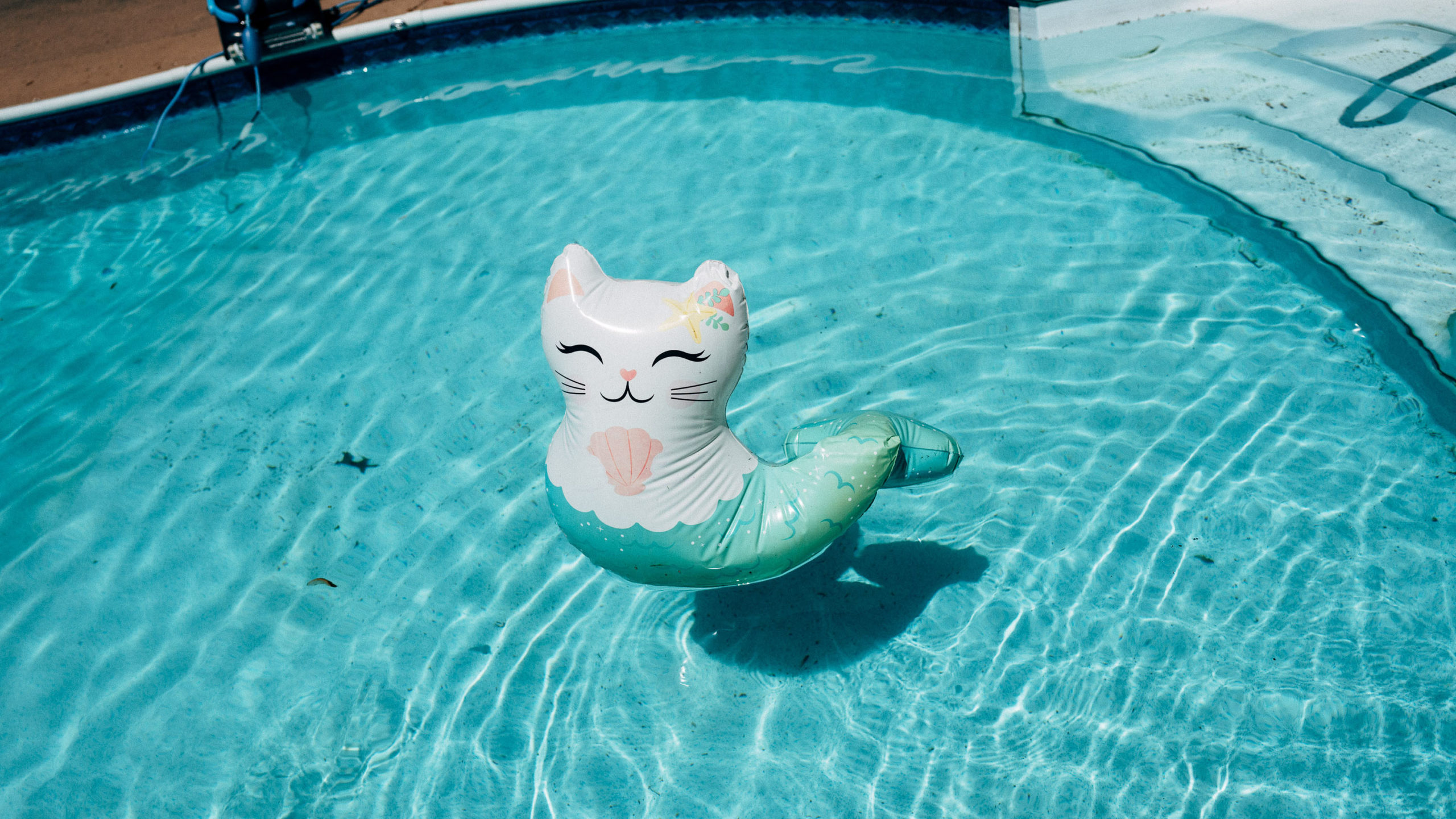 An inflatable cat mermaid float in a pool
