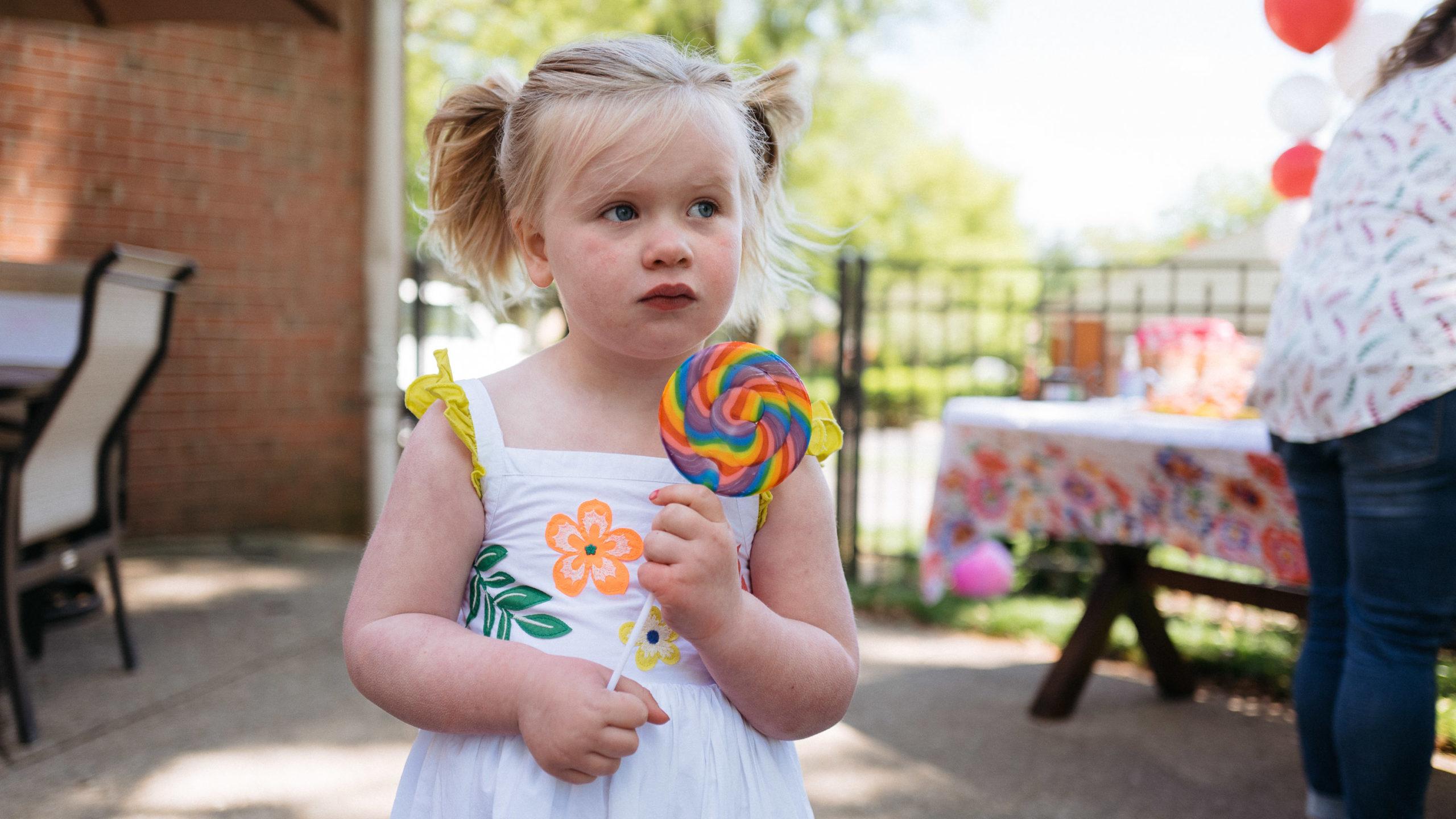 A young girl has a rainbow lollipop and a curious glance