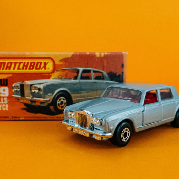 A 1/8 scale Rolls Royce Matchbox car on a yellow background
