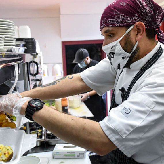 A man works in food service, probably not making a living wage