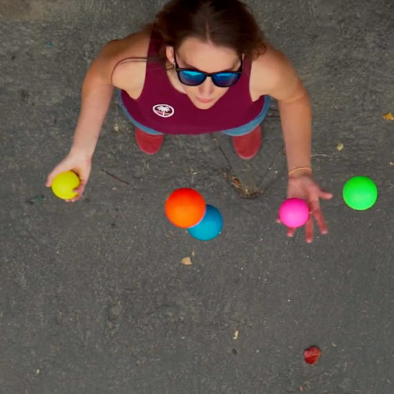 A woman juggles 5 different colored balls, filmed from above