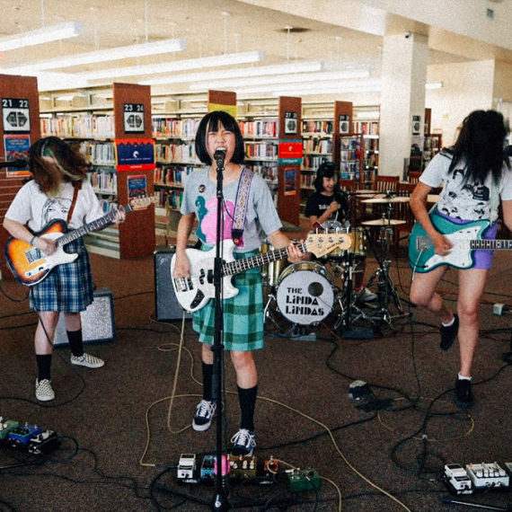 A rock band comprised of four young women performing a song in a library